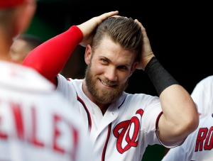 In this photo taken May 19, 2015, Washington Nationals right fielder Bryce Harper (34) reacts in the dugout during an interleague baseball game against the New York Yankees at Nationals Park in Washington. There's rarely a dull moment when it comes to Bryce Harper. Been that way pretty much ever since the Washington Nationals brought him to the majors at age 19. He'll hit six home runs in a span of three games. He'll get ejected twice in the span of seven days. He'll win NL Player of the Week honors _ and then do it again a week later. And all of that has happened just this month. (AP Photo/Alex Brandon) ORG XMIT: WX201
